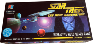 The lid of the Star Trek: A Klingon Challenge box depicting the Enterprise 1701D flying through a star system with the face 'Kavok', the Klingon who takes the Enterprise, on the right hand side.