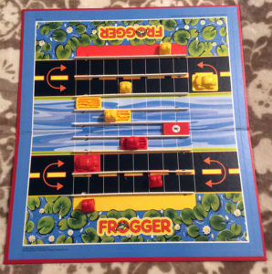 Frogger: The board game playing board and playing pieces. The board shows lily pads top and bottom with a section of road immediately after. In the middle is a river. There is a red car on one road and a yellow car on the other. In the river there are red and yellow logs which can be flipped to show a bonus. There are three frogs of each colour, red and yellow, attempting to crossover to the opposite set of lily pads via each turn.