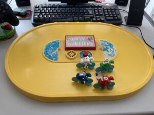 a 1970s Whirly Wheelers game showing toy cyclists on a yellow track preparing to race.